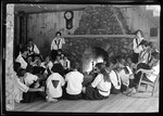 Group Of Girls Sitting Around The Fireplace At Camp by George French