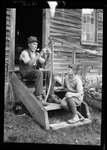 Older Man Sitting On Steps While Stringing A Bow For A Young Boy. by George French