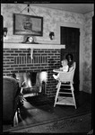 Baby In High Chair In Front Of Fireplace With Fire Lit by George French