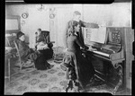 """Girl Playing Piano While Family Looks On. """"Girl At Piano"""" by George French"""