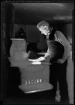 George French Putting A Piece Of Wood In Kitchen Stove. by George French