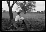 Don French Sitting On Log Under Apple Tree, Reading by George French