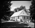 Two Ladies Out Front Of Cape Style House Holding Hand Made Items In Sandwich, New Hampshire by George French