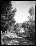 Looking Down Road To Village, Steeple Of Church Sticks Up In Front Of Mountain In Grafton, Vermont by George French