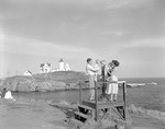 Family Stands At Binocular Viewing Area Across From Nubble Lighthouse In York by George French