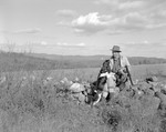 Herb Sits On Stone Wall Petting His Dog While Holding Birds And Gun, Fields In Behind In Kezar Falls by George French