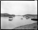 Lobsterman Rows Punt Out To Lobster Boat Loaded With Traps, Hills And Harbor Surround In Bucks Harbor by George French