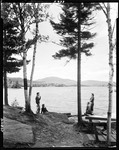 People Standing On Shore Of Moosehead Lake, Mountains In Distance by George French