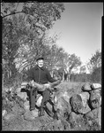 Goodwin Sits On Stone Fence With Rifle And A Fox, Woods And House Afar--Parsonsfield by George French