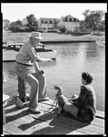 Man Fishing With Hand Line, Sitting On Piling, Girl Sits On Dock With Dog And Watches, Close-up--ogunquit by George French