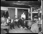 Ern Playing An Accordion, I Playing A Banjo, Mable Putting Wood In Stove, MassachusettsHolding A Cat Two Others In Basket On Floor by George French