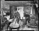 Ern Sitting Next To Stove While Whittling, Old Man Shaving Wood, Both In A Workshop In Kezar Falls by George French