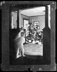 George French And His Wife Putting Last Touches On Christmas Tree Fully Loaded With Gifts, Don French And His Sister Look On. by George French
