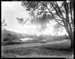 Car On A Road Paralleling A Stream In Porter, Hills In Background by French George