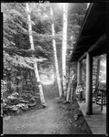 Boy Standing By A Cottage In The Woods Holding A Fishing Rod, Lady Sitting On Porch Reading A Book At The Birches, Moosehead by George French
