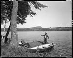 Man Sitting On Dock Watching Another In Canoe About To Go Fishing In Lovell by George French