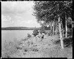 Older Couple Sitting In Lawn Chairs By The Water At Shin Pond, He Fishing by George French