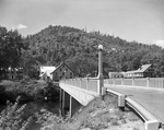 Highway Bridge Over A Stream In Hiram, Houses And A Hill In Background by George French