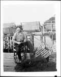 Fisherman Sitting On Dock Repairing Fish Net In New Harbor by George French