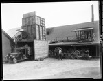 Factory With Truck At Loading Dock And A Trailer Loaded With Bushels Of Corn Nearby by George French