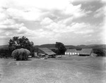 Barn And Farmhouse Against Backdrop Of Distant Mountains, Loaded Hay Wagon In Foreground by George French