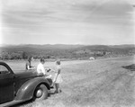 Family Near A Car Parked In A Field With Nice View Of Distant Mountains by George French