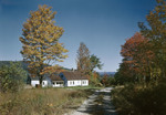 Dirt Road Past Farmhouse In Brownfield, Mountains In Distance In Fall by George French