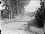 Car Driving On A Rural Road Past A House by George French
