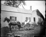Elderly Couple Sitting In A Horse Drawn Buggy Outside A Farm House by George French