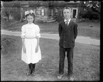 A Young Boy & Girl, Dressed Up, Standing Outside Of A Home by George French