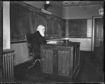 College Professor Seated At His Desk In A Classroom (Bates College) by George French