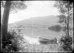 Canoe Pulled Up On A Lake Shore, Mountains In The Distance by George French
