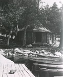 Log Cabin by a Lake with Canoes