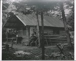 Log Cabin with Man Seated Outside