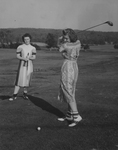 Two Women in Dresses Playing Golf