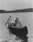 Two Women in Bathing Suits Rowing a Canoe Across a Maine Lake by Maine Development Commission