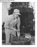 Man Working Onboard a Trawler Holding a Fish by Department of Marine Resources