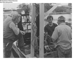 Docked Vessel with Two Men and Clams on Board while Two Men on the Dock Lean in for a Look by Maine Department of Marine Resouces