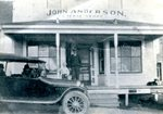 John Anderson & child in front of Anderson's store.